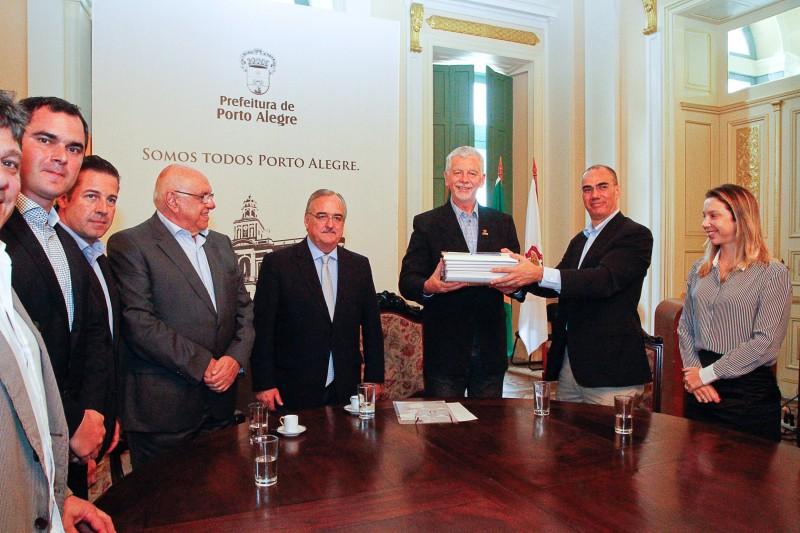 Abreu (2ª à dir) repassou volumes da proposta ao prefeito Fortunati