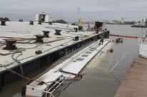 Após tempestade, equipes de trabalho tentam desvirar a embarcação