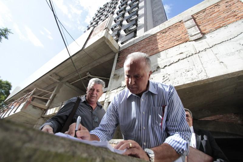 Vitor Silveira assina documento relativo ao cumprimento do mandado diante do prédio