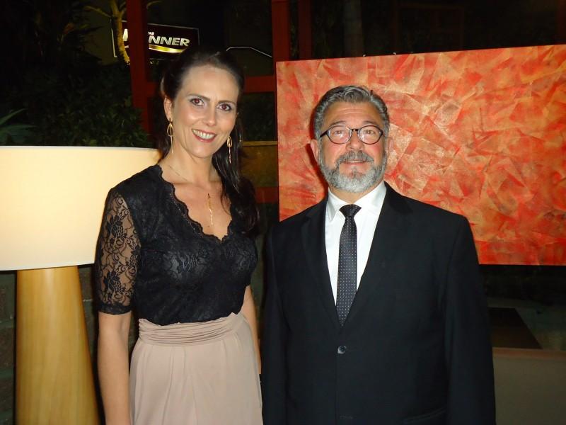 Maria Rita Kops e Paulo Zoppas em seu espaço, com obra de Claudio Cupertino ao fundo