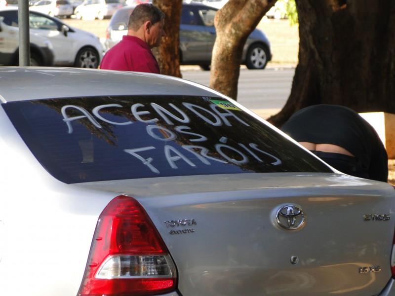 Aviso em táxi de Brasília alerta para a nova regra dos faróis ligados