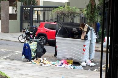 Catador retirando lixo seco de dentro de contêiner na rua Tobias da Silva, bairro Moinhos de Vento