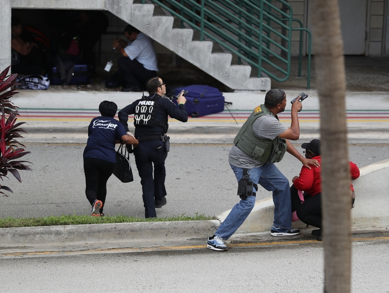 FORT LAUDERDALE, FL - JANUARY 06: Police assist people seeking cover outside of Terminal 2 at Fort Lauderdale-Hollywood International airport after a shooting took place near the baggage claim on January 6, 2017 in Fort Lauderdale, Florida. Officials are reporting that five people wear killed and eight wounded in an attack from a single gunman.   Joe Raedle/Getty Images/AFP