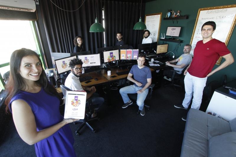 Juliana (esq.) e Pedro (dir.), CEOs do aplicativo Joyz com a equipe da Aioria, desenvolvedora técnica
