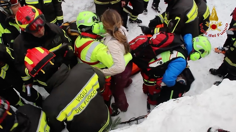 A handout picture released on January 20, 2017 by the Vigili del Fuoco shows a woman being rescued from the Hotel Rigopiano, near the village of Farindola, on the eastern lower slopes of the Gran Sasso mountain, engulfed by a powerful avalanche a day before.