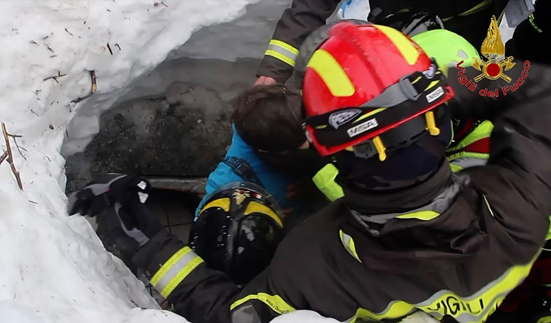 A handout picture released on January 20, 2017 by the Vigili del Fuoco shows a child (C) being rescued from the Hotel Rigopiano, near the village of Farindola, on the eastern lower slopes of the Gran Sasso mountain, engulfed by a powerful avalanche a day before.