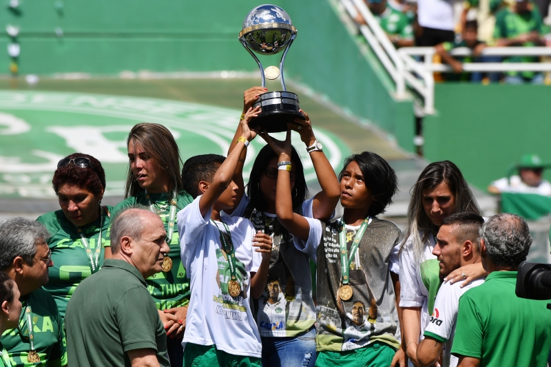 Relatives of players who died in the LaMia airplane crash in Colombia hold the Copa Sudamericana trophy at the Arena Conda stadium in Chapeco, Santa Catarina state, in southern Brazil on January 21, 2017, before a friendly match against Palmeiras - Brazilian Champion 2016. 