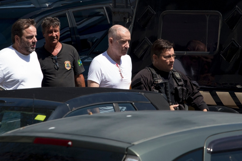 Brazilian businessman Eike Batista (2-R) is escorted as he leaves the Federal Police headquarters after a hearing in Rio de Janeiro, Brazil on February 8, 2017.  Brazil's former richest man, Batista, was jailed last week on charges of corruption, money laundering and criminal organization.  / AFP PHOTO / Mauro PIMENTEL