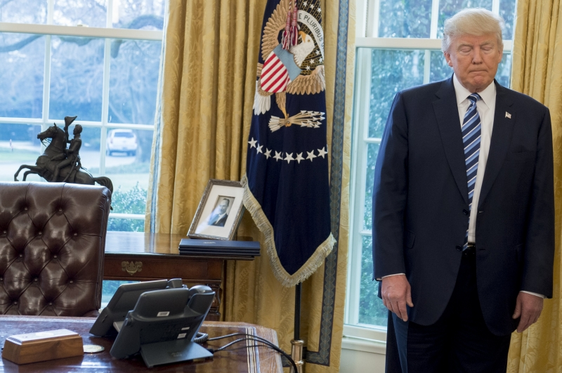 US President Donald Trump stands behind his desk after Jeff Sessions was sworn in as Attorney General in the Oval Office of the White House in Washington, DC, February 9, 2017. / AFP PHOTO / SAUL LOEB       Caption