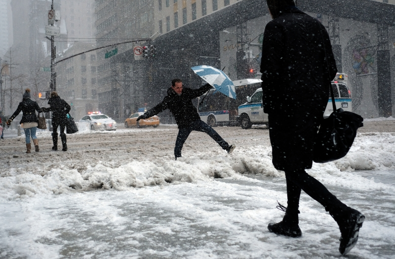 People make their way during a winter storm in New York on February 9, 2017. A heavy winter snow storm lashed the northeastern United States Thursday, subjecting New York to near blizzard-like conditions and forcing flight cancellations as schools and the United Nations closed. / AFP PHOTO / Jewel SAMAD
