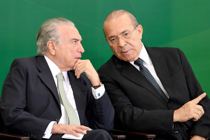 Brazilian President Michel Temer (L) and Chief of Staff Eliseu Padilha talk during a ceremony to announce measures to make access to labour rights more flexible at Planalto Palace in Brasilia on February 14, 2017. The Government expects the injection of R$ 40 billion (around U$ 13 billion) in the economy with the access of workers to amounts retained in the guarantee fund. / AFP PHOTO / EVARISTO SA       Caption