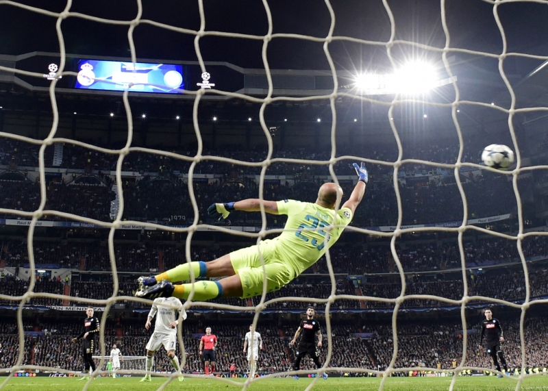 Napoli's goalkeeper from Spain Pepe Reina (C) dives for the ball as Real Madrid's Brazilian midfielder Casemiro scores a goal during the UEFA Champions League round of 16 first leg football match Real Madrid CF vs SSC Napoli at the Santiago Bernabeu stadium in Madrid on February 15, 2017.