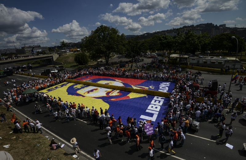 Supporters of jailed Venezuelan opposition leader Leopoldo Lopez surround a giant image of him during a demonstration held on the third anniversary of his arrest, on the main highway in Caracas on February 18, 2017. 