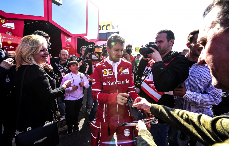Ferrari's German driver Sebastian Vettel signs autographs at the Circuit de Catalunya on February 27, 2017 in Montmelo on the outskirts of Barcelona during the first day of the first week of tests for the Formula One Grand Prix season.  / AFP PHOTO / JOSE JORDAN