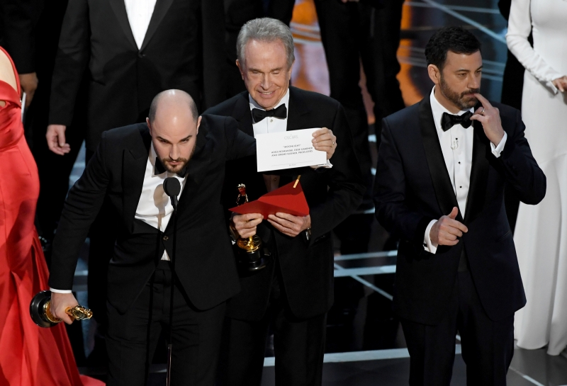 HOLLYWOOD, CA - FEBRUARY 26: 'La La Land' producer Jordan Horowitz (L) holds up the winner card reading actual Best Picture winner 'Moonlight' after a presentation error with actor Warren Beatty and host Jimmy Kimmel onstage during the 89th Annual Academy Awards at Hollywood & Highland Center on February 26, 2017 in Hollywood, California.   Kevin Winter/Getty Images/AFP       Caption