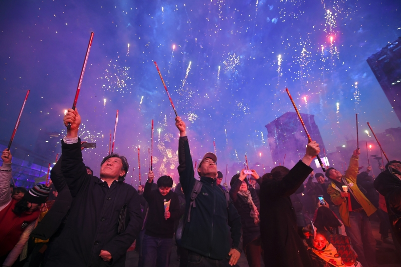 South Korean demonstrators shoot off firecrackers to celebrate the impeachment of Park Geun-Hye during a candlelit rally demanding arrest of Park Geun-Hye in Seoul on March 11, 2017. South Korea's ousted leader Park Geun-Hye was holed up in the presidential Blue House Saturday as protesters took to Seoul's streets demanding her arrest, a day after a court upheld her impeachment.   Coréia do Sul, Seul, manifestação
