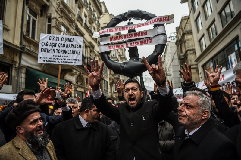People hold a symbolic black wreath in front of the Netherlands consulate as they demonstrate on March 11, 2017, in Istanbul. Turkish President Recep Tayyip Erdogan on March 11, likened a Dutch ban on his foreign minister's visit to Nazism, in a dramatic escalation of a row over campaign events abroad for Turkey's high stakes referendum. The leader's strongly-worded comments came after The Hague said it would refuse Foreign Minister Mevlut Cavusoglu's plane permission to land ahead of a rally to gather support for boosting Erdogan's powers.