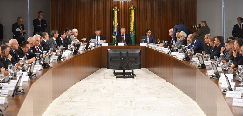 Brazilian President Michel Temer (C), Agriculture Minister Blairo Maggi (C-L) and Industry and Commerce Minister Marco Pereira (C-R) meet with ambassadors from countries that import Brazilian meat, at the Planalto Palace in Brasilia on March 19, 2017.  The revelation on Friday of a two-year police probe into alleged bribery of health inspectors to certify tainted food as fit for consumption has struck at the heart of the world's leading exporter of beef and chicken.  / AFP PHOTO / EVARISTO SA       Caption