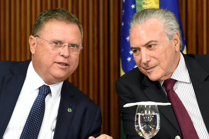 Brazilian President Michel Temer (R) and his Agriculture Minister Blairo Maggi talk during a meeting with ambassadors from countries that import Brazilian meat at Planalto Palace on March 19, 2017. 