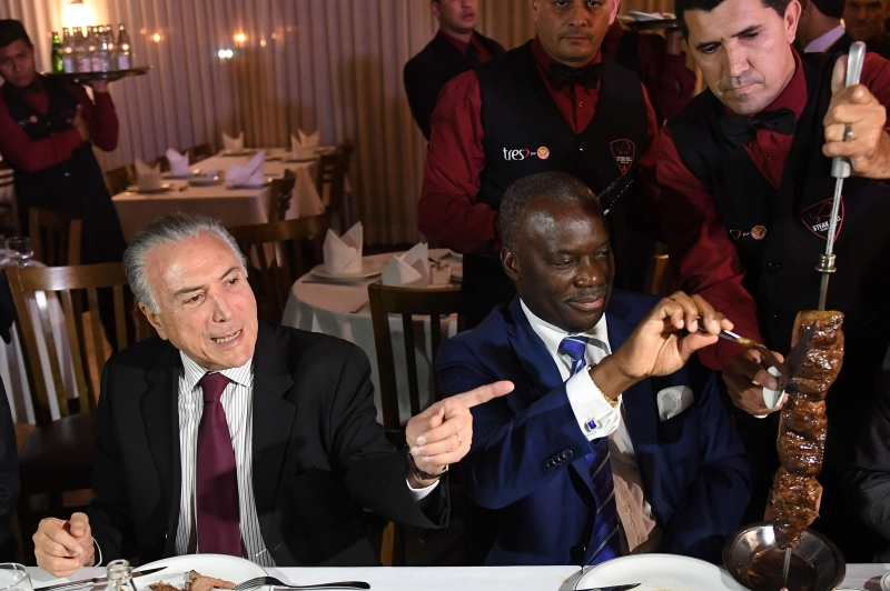 Brazilian President Michel Temer and Angola's ambassador Nelson Manuel Cosme eat barbecue in a steak house in Brasilia after a meeting with ambassadors from countries that import Brazilian meat, on March 19, 2017. 