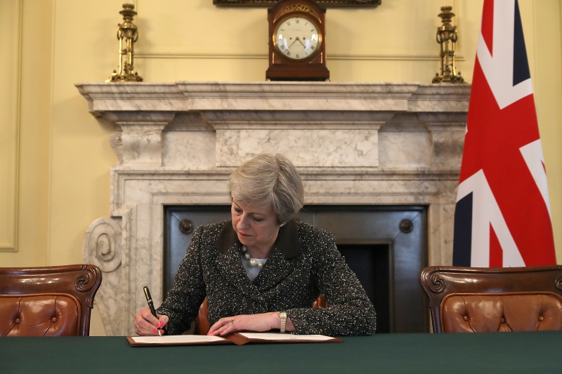 Britain's Prime Minister Theresa May, signs the official letter to European Council President Donald Tusk, invoking Article 50 and signalling the United Kingdom's intention to leave the EU, in the cabinet office inside 10 Downing Street on March 28, 2017.. British Prime Minister Theresa May will send a letter to EU President Donald Tusk with Britain's formal departure notification on Wednesday, opening up a two-year negotiating window before Britain actually leaves the bloc in 2019. / AFP PHOTO / POOL / CHRISTOPHER FURLONG       Caption