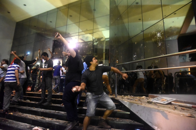 Hundreds of demonstrators protesting against the approval of a constitutional amendment for presidential reelection broke into the Congress building, battering down entrances and fences and shattering windows, and started to set fires inside, in Asuncion on March 31, 2017.