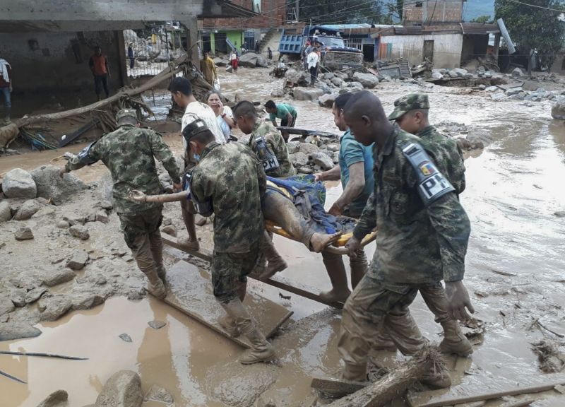 Handout picture released by the Colombian Army press office showing soldiers carrying a corpse following mudslides caused by heavy rains, in Mocoa, Putumayo department, on April 1, 2017.