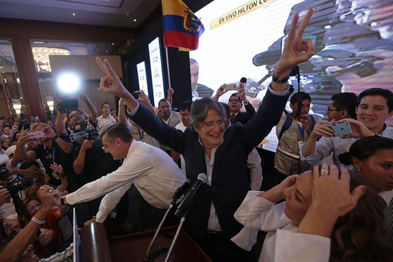Ecuadorean presidential candidate Guillermo Lasso and his family and supporters celebrate that he is in the lead, as they listen to the first results of the runoff election in Guayaquil, Ecuador on April 2, 2017. / AFP PHOTO / JUAN CEVALLOS