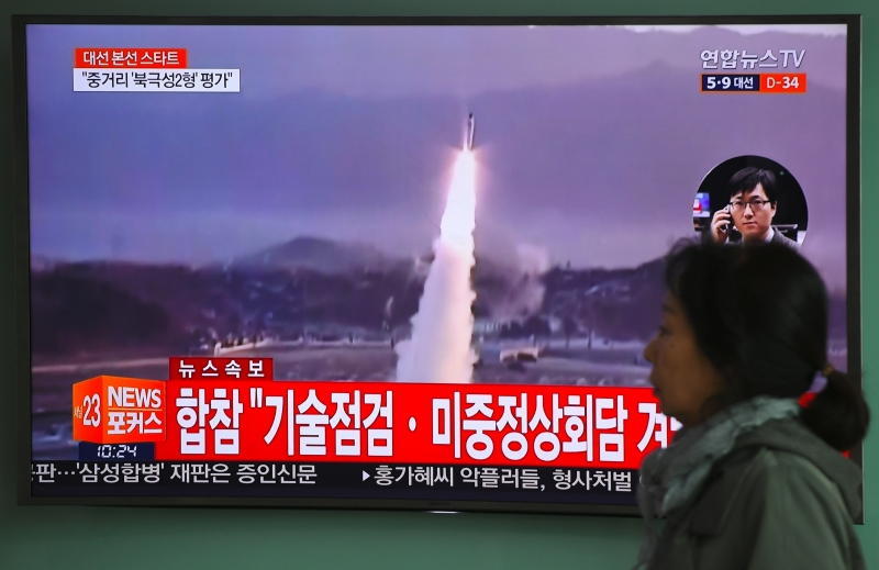 A woman walks past a television screen showing file footage of a North Korean missile launch, at a railway station in Seoul on April 5, 2017. Nuclear-armed North Korea fired a ballistic missile into the Sea of Japan on April 5, just ahead of a highly-anticipated China-US summit at which Pyongyang's accelerating atomic weapons programme is set to top the agenda. / AFP PHOTO / JUNG Yeon-Je