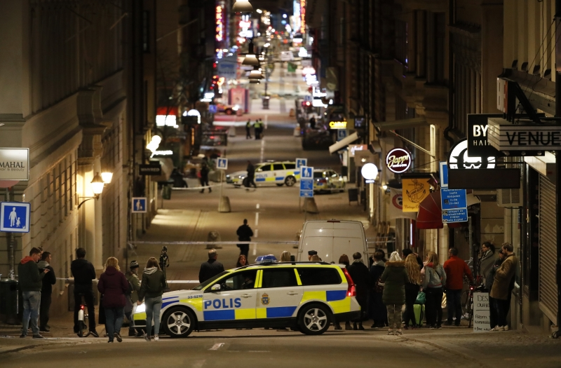 People stand behind the cordon as the police work at the scene after a truck slammed into a crowd of people outside a busy department store in central Stockholm, causing