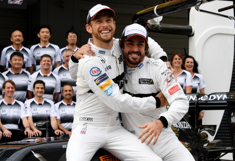 (FILES) This file photo taken on October 7, 2016 shows McLaren Honda's British driver Jenson Button (L) joking with his teammate Fernando Alonso of Spain (R) during the team's photo session at the Formula One Japanese Grand Prix in Suzuka.
