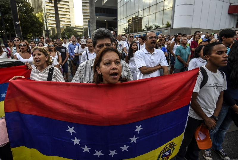 Venezuelan opposition activists march during a protest against President Nicolas Maduro's government, in Caracas on April 15, 2017. Venezuelan authorities said Friday they had arrested two opposition youth leaders, the latest move in a crackdown against ongoing anti-government protests that have left five people dead. / AFP PHOTO / JUAN BARRETO       Caption