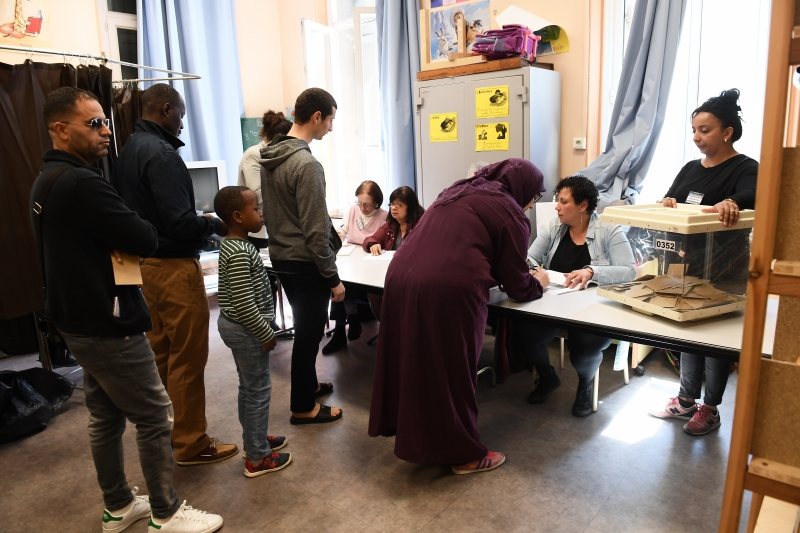 Voters queue at a polling station in Marseille, southern France, on April 23, 2017 during the first round of the French presidential election.  / AFP PHOTO / 