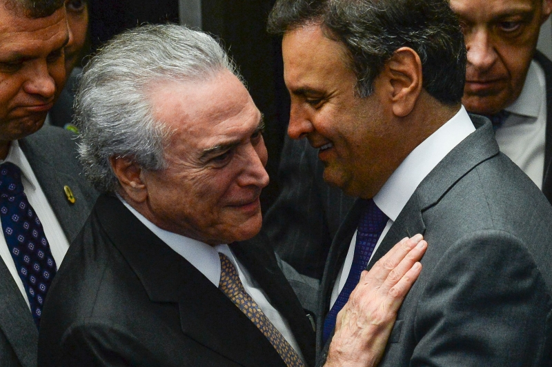 (FILES) This file photo taken on August 31, 2016 shows President Michel Temer (L) speaks with senator Aécio Neves in Brasilia. Brazil's President Michel Temer reeled on May 18, 2017 from a report that he authorized payment of hush money to a jailed politician in a scandal threatening to plunge Latin America's biggest country into political meltdown. In another blow for the veteran leader of the center-right PMDB party, his key ally Senator Aecio Neves from the PSDB party was targeted by anti-graft police early Thursday. / AFP PHOTO / ANDRESSA ANHOLETE