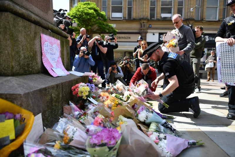 Police officers relocate floral tributes in St Ann's Square in Manchester, northwest England on May 23, 2017, laid as a mark of respect to those in killed and injured following a deadly terror attack at the concert at the Manchester Arena the night before. 