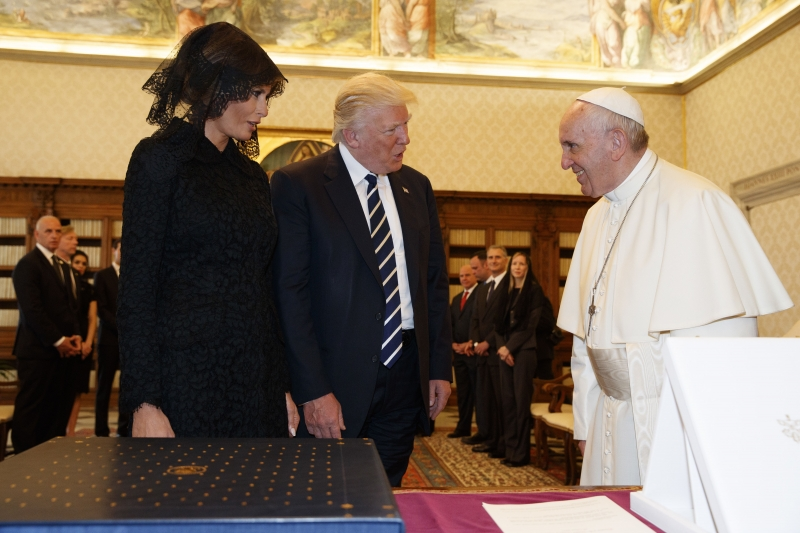 Pope Francis (R) exchanges gifts with US President Donald Trump and US First Lady Melania Trump during a private audience at the Vatican on May 24, 2017. US President Donald Trump met Pope Francis at the Vatican today in a keenly-anticipated first face-to-face encounter between two world leaders who have clashed repeatedly on several issues. / AFP PHOTO / POOL / Evan Vucci