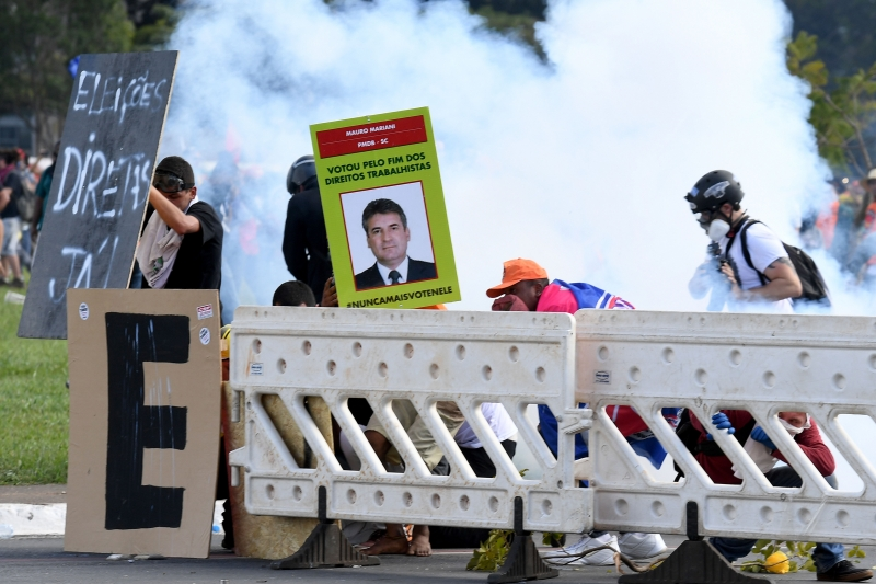Protesters face tear gas as they clash with police during the protest