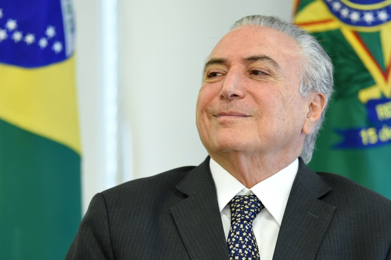 Brazilian President Michel Temer gestures during a meeting with  businessmen at Planalto Palace in Brasilia, on May 25, 2017. Brazilian soldiers deployed Wednesday to defend government buildings in the capital Brasilia after protesters demanding the exit of President Michel Temer smashed their way into ministries and fought with riot police. / AFP PHOTO / EVARISTO SA