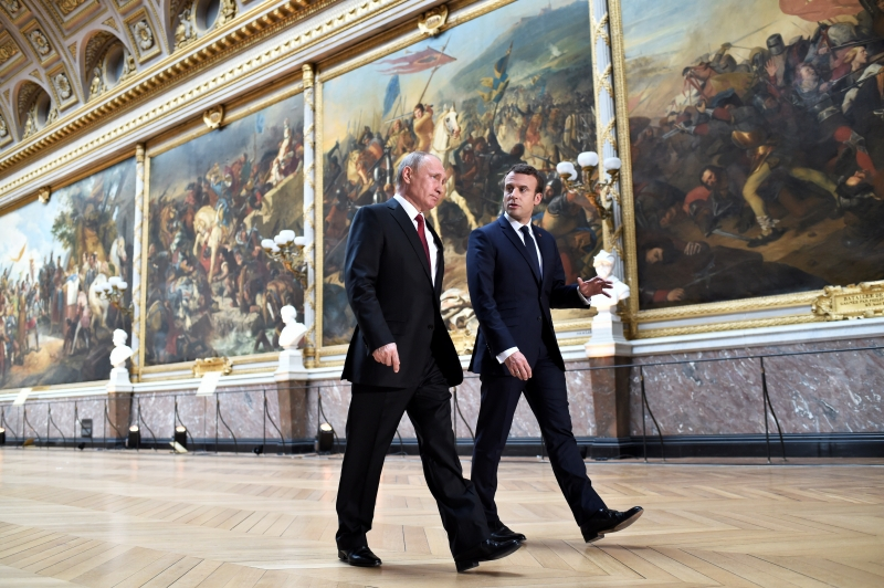French President Emmanuel Macron (R) speaks to Russian President Vladimir Putin (L) in the Galerie des Batailles (Gallery of Battles) as they arrive for a joint press conference following their meeting at the Versailles Palace, near Paris, on May 29, 2017.