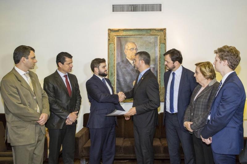 Gabriel Souza (terceiro à esq.) entrega texto do decreto a Edegar Pretto