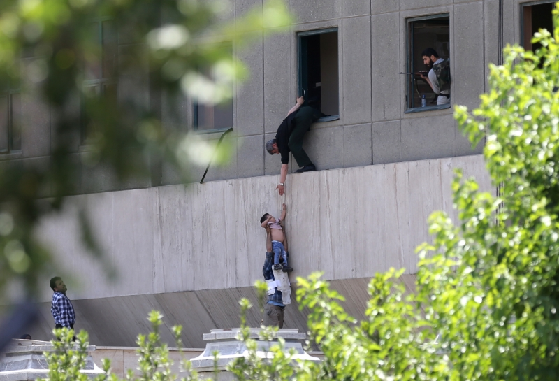 Iranian policemen evacuate a child from the parliament building in Tehran on June 7, 2017 during an attack on the complex.    The Islamic State group claimed its first attacks in Iran as gunmen and suicide bombers killed at least five people in twin assaults on parliament and the tomb of the country's revolutionary founder in Tehran. / AFP PHOTO / FARS NEWS / OMID VAHABZADEH