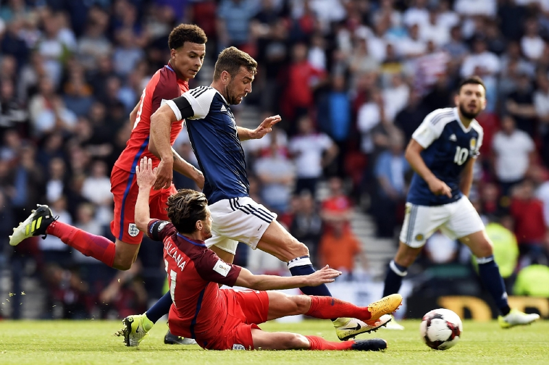 England's midfielder Adam Lallana (R) slides in to tackle Scotland's midfielder James McArthur (C) during the group F World Cup qualifying football match between Scotland and England at Hampden Park in Glasgow on June 10, 2017. The game ended 2-2. / AFP PHOTO / ANDY BUCHANAN / NOT FOR MARKETING OR ADVERTISING USE / RESTRICTED TO EDITORIAL USE