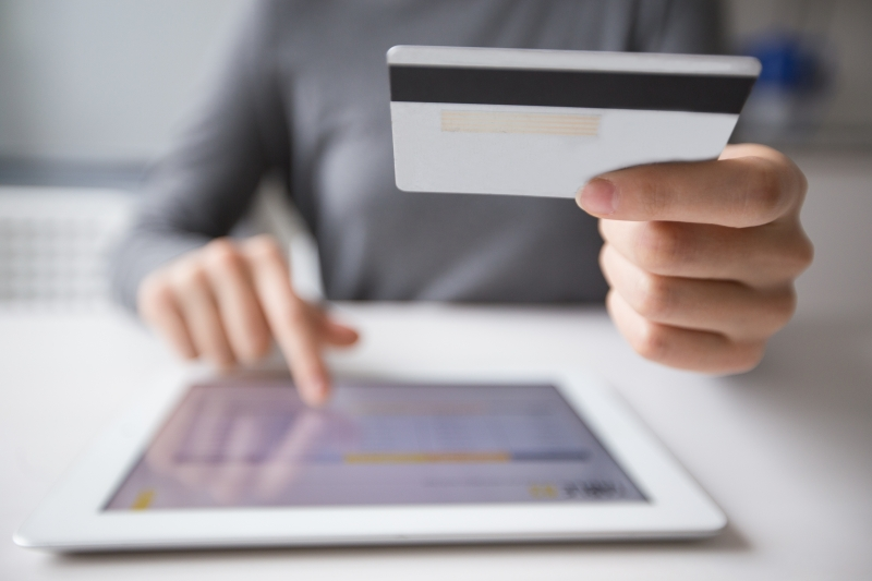 Cropped view of woman making online payment on tablet computer and holding credit card with focus on card   Contabilidade - iss cartão de crédito - divulgação Katemangostar - Freepik.com