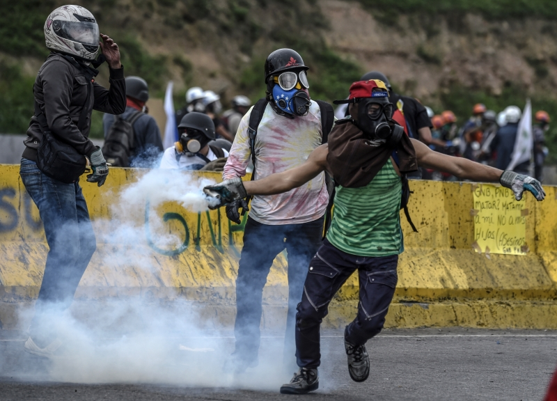 An opposition activist throws tear gas back at riot police in clashes at the Francisco de Miranda air force base during a demonstration against the government of Venezuelan President Nicolas Maduro in Caracas on June 24, 2017, near the place where a young man was shot dead by police during an anti-government rally two days ago.