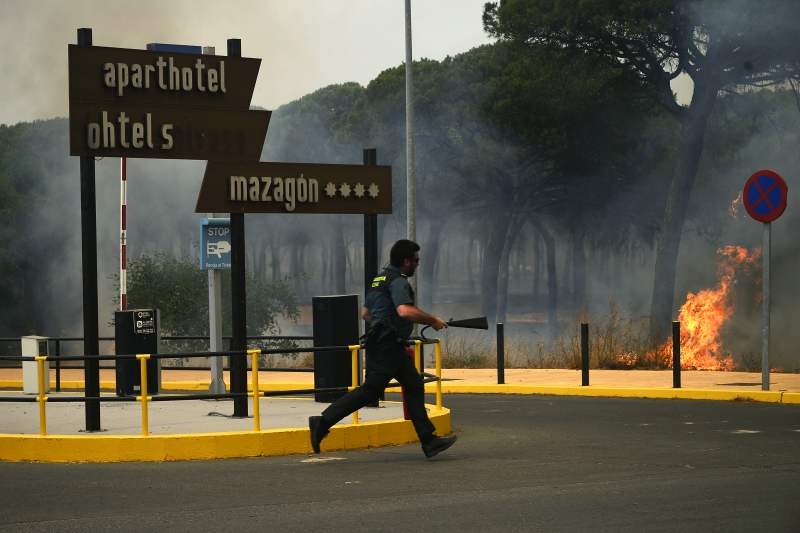 A Spanish Guardia Civil runs with an extinctor during a wildfire in Mazagon, on July 25, 2017.