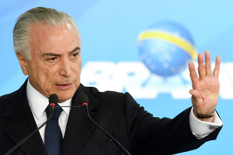 Brazilian President Michel Temer speaks during the signing ceremony of the decree that frees differential prices for payment in cash and with credit card at the Planalto Palace in Brasilia, on June 26, 2017.  Temer faces his own crisis with the prosecutor general expected to request formal corruption charges against the president Monday or Tuesday. / AFP PHOTO / EVARISTO SA       Caption