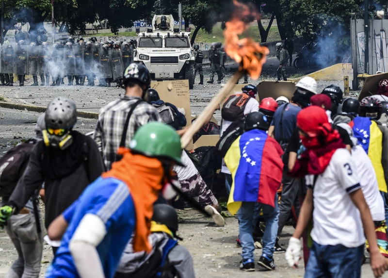 Opposition activists clash with riot police during a march towards the Supreme Court of Justice (TSJ) in an offensive against President Maduro and his call for Constituent Assembly in Caracas on July 22, 2017.
