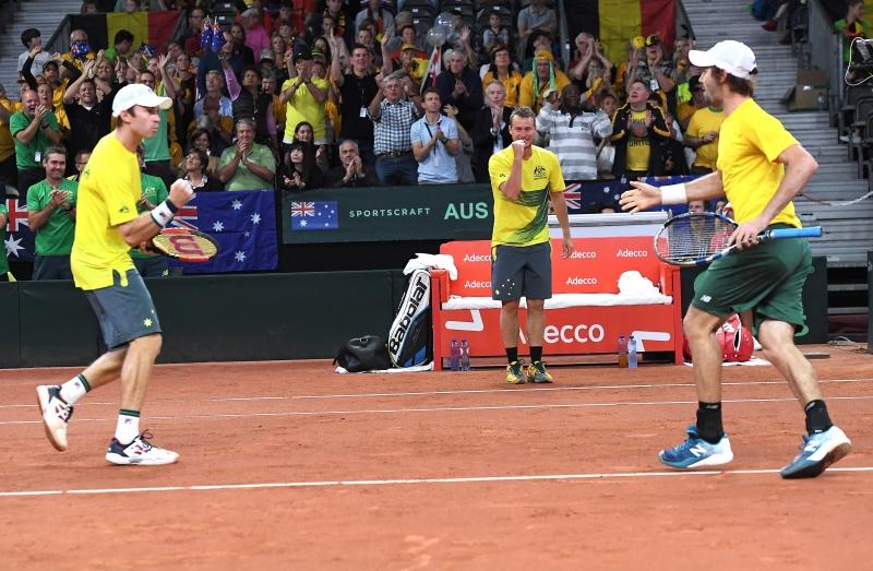 Lleyton Hewitt (c), Jordan Thompson (d) e John Peers comemoram a vitória da Austrália contra a Bélgica