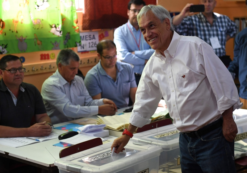 Chilean presidential candidate Sebastian Pinera casts his vote during the presidential election in Santiago on November 19, 2017. Voting began Sunday in the first round of Chile's presidential election, with former president Sebastian Pinera likely to cement his frontrunner status to succeed Socialist leader Michelle Bachelet. / AFP PHOTO / Martin BERNETTI       Caption