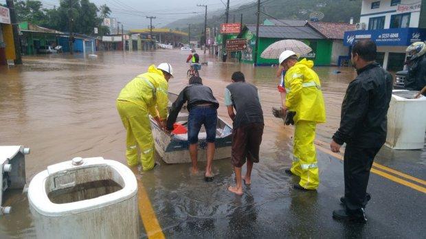 Em Florianópolis, funcionários da companhia de energia tentam acessar de barco área alagada